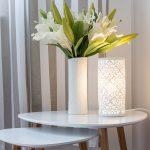 Romantické zátišie z vázy s kvetmi a bielym perforovaným svietnikom.