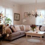 vianočne zariadená obývačka s rohovým gaučom v neutrálnej farbe, na ktorom je veľa vankúšov v odtieňoch bielej a hnedej, s bielym stolíkom s vysokými svietnikmi a vázou s čečinou a kvetinami, mäkkým kobercom a vianočným stromčekom s prírodnými ozdobami