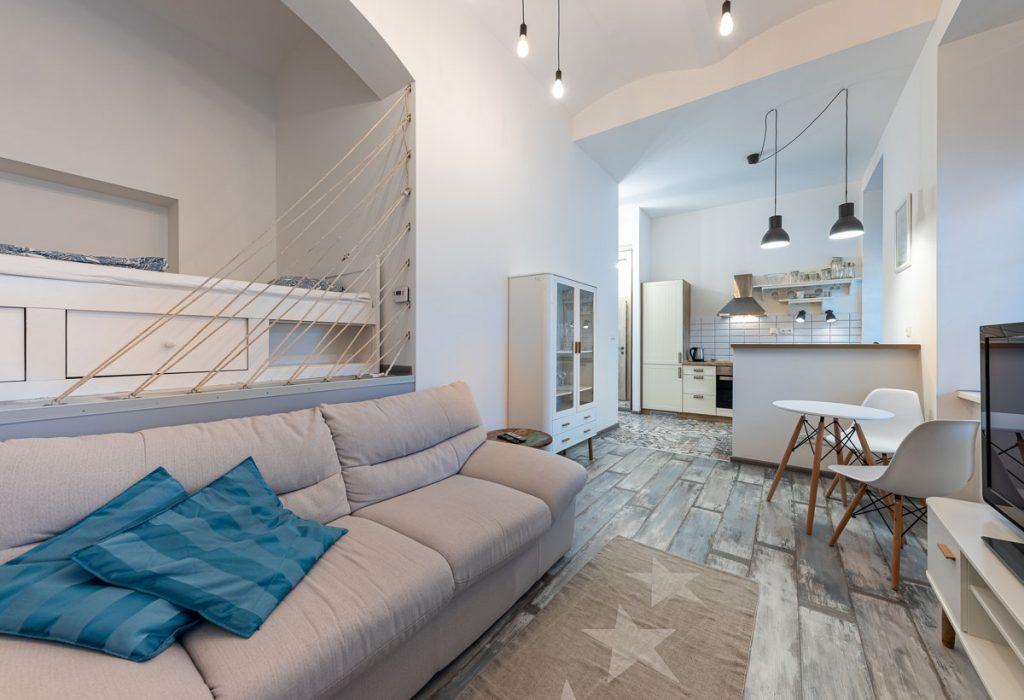 obývačka spojená s kuchyňou v malom byte, so sivou sedačkou, výklenkom s pódiom na spanie a kuchyňou v retro štýle