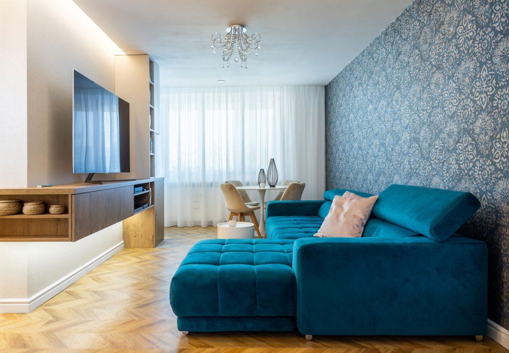 Obývačka s veľkoformátovou modrou vzorovanou tapetou, modrou rozkladacou pohovkou, jedálenským stolom a TV stenou plynule prechádzajúcou do kuchynskej linky.