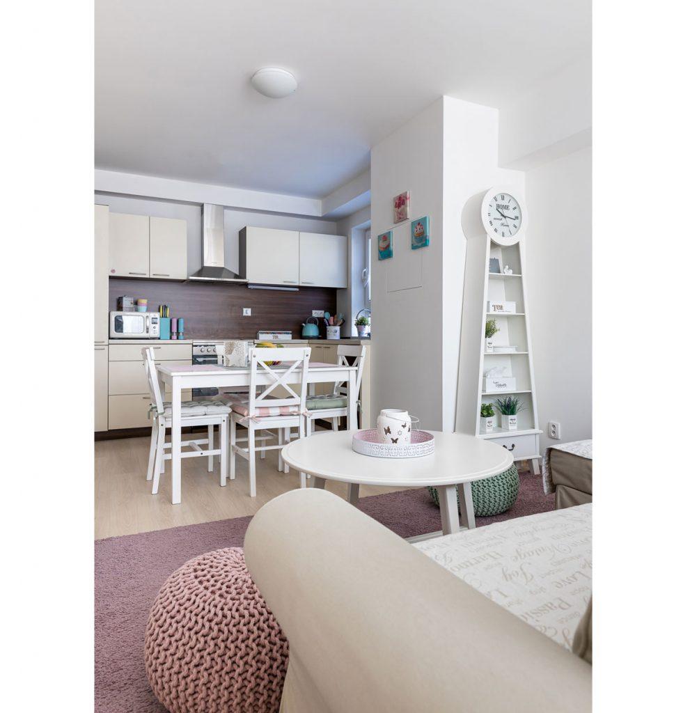Spojenie obývačky a kuchyne v malom byte. Priestor je zariadený vo vintage a vidieckom štýle.