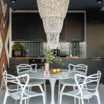 kuchyňa s čiernou linkou a čiernym stropom, elegantným korálkovým lustrom, jedálenským stolom Tulip a stoličkami Masters