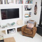 stena v interiéri so zavesenou TV a členitou bielou knižnicou, vedľa stojí hnedé retro kreslo