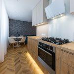 Kuchynská linka z drevodekoru, so skrinkami v béžovej farbe a s podsvietením.