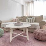 Obývačka v romantickom vidieckom štýle s pohovkou v neutrálnej farbe, pastelovým ružovým a zeleným pufom, ružovým kobercom a vidieckym okrúhlym stolíkom.
