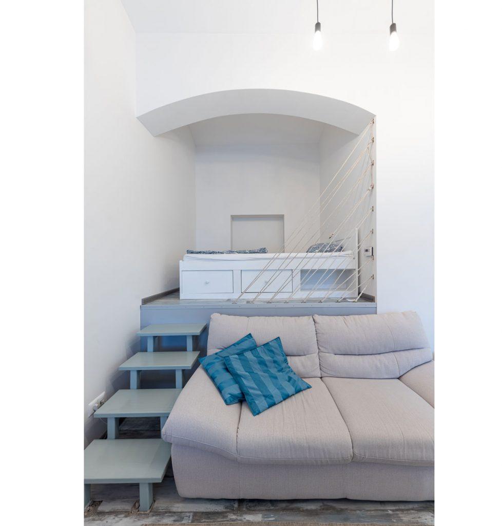 spálňa v malom byte postavená na vyvýšenom pódiu a oddelená lanami od obývacej časti