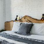 spálňa zariadená v prírodnom duchu s dreveným neopracovaným čelom postele a ľanovým posteľným prádlom v sivo-bielej kombinácii