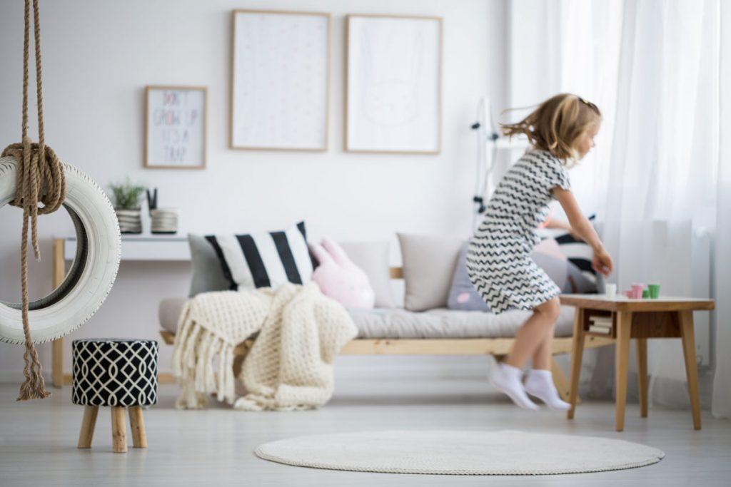 malé dievča skáče v obývačke