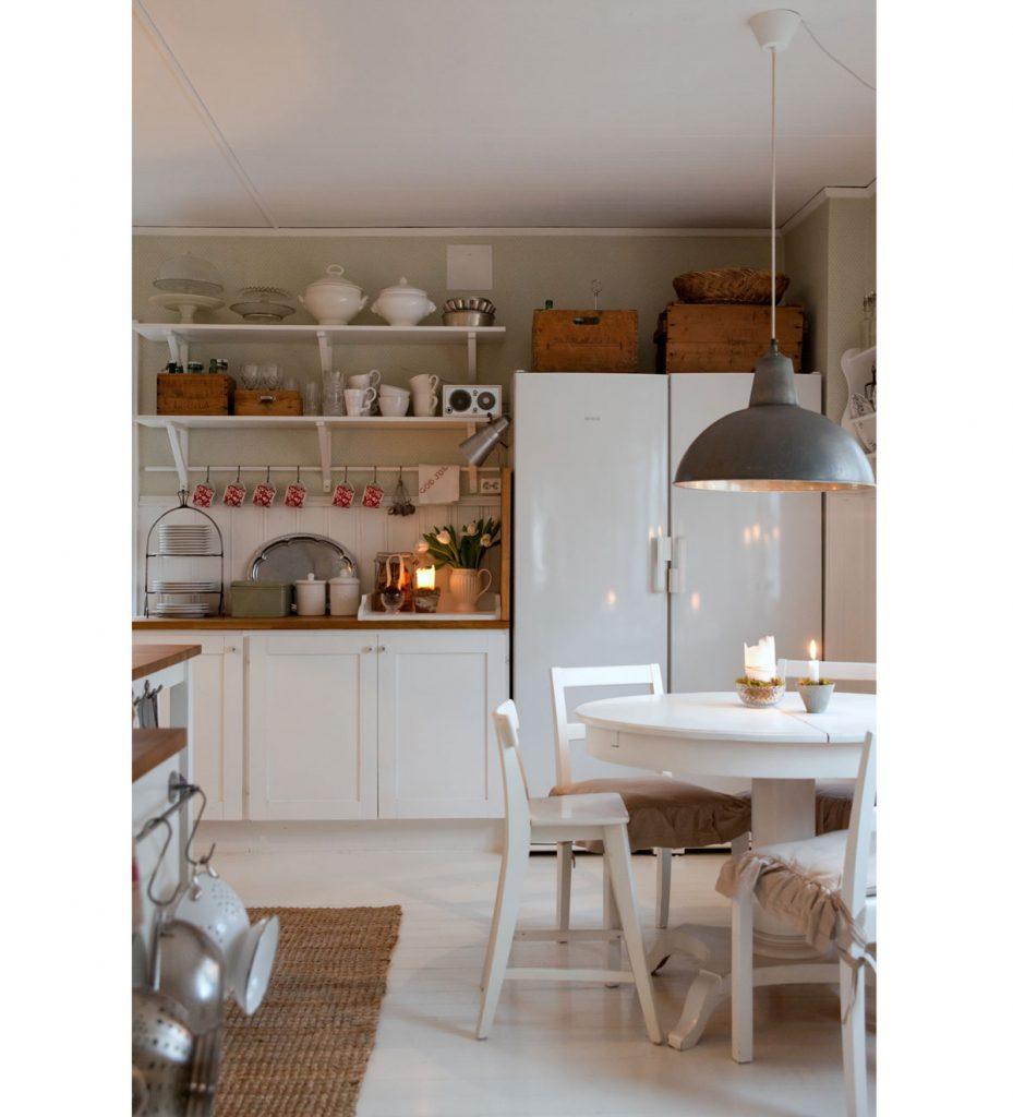 kuchyňa vo vidieckom škandinávskom štýle s bielym okrúhlym rozkladacím stolom, bielymi stoličkami, bielou kuchynskou linkou, pleteným prírodným behúňom a otvorenými policami, na ktorých sú poukladané riady a staré drevené truhlice