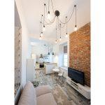 malý byt s kuchyňou a obývaciu miestnosťou v industriálnom štýle s tehlovou stenou
