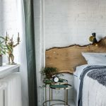 spálňa zariadená v prírodnom duchu s dreveným neopracovaným čelom postele, ľanovým posteľným prádlom v sivo-bielej kombinácii a metalickými okrúhlymi nočnými stolíkmi