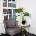 interiér s retro čalúneným kreslom, kobercom s geometrickým vzorom, art déco stolíkom s mramorovou doskou a zlatými nohami, na stolíku stojí veľká okrasná rastlina