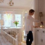 žena zapaľuje sviečky v interiéri vo vidieckom štýle, s bielou drevenou posteľou, bielou komodou a bielym pracovným stolom, interiér osvetľuje svetelná reťaz na veľkom zrkadle a perforovaná papierová svietiaca hviezda