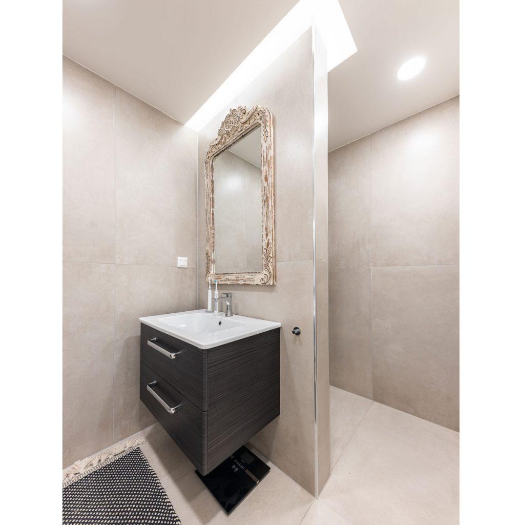 Kúpeľňa s veľkorozmernými obkladmi a so sprchovacím kútom oddeleným priečkou, na ktorej je pripevnené umývadlo.