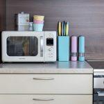 Kuchynská linka s mikrovlnkou a farebnými miskami, koreničkami a stojanom na nože.