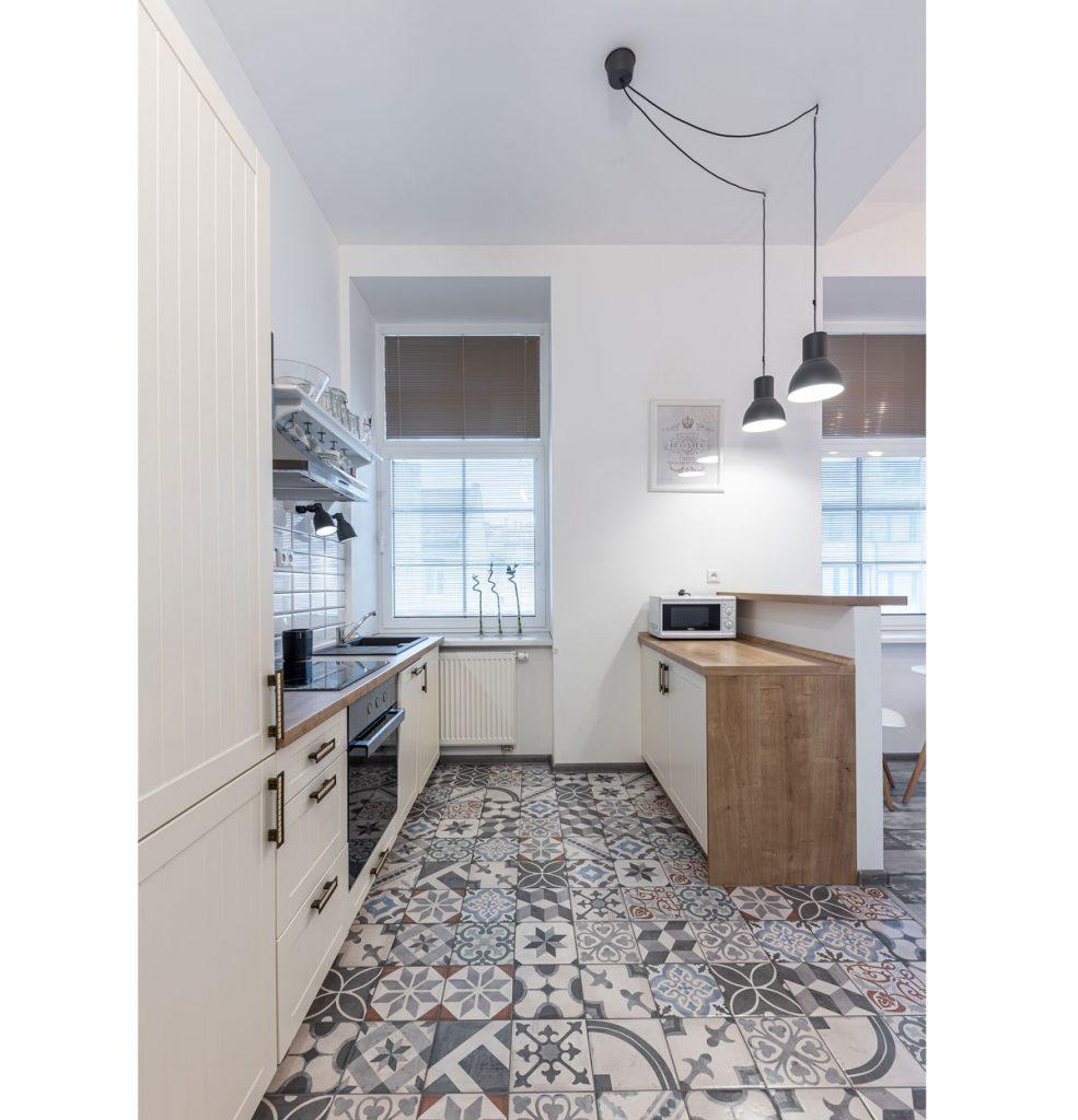 kuchyňa so vzorovanou podlahou, bielou kuchynskou linkou vo vidieckom štýle a doplnkami v industriálnom štýle