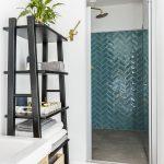 kúpeľňa s čiernym regálom a sprchovým kútom a kachličkami akvamarínovej farby cikcakového vzoru