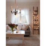 škandinávsky vidiecky interiér vyzdobený na Vianoce, so sedačkou a pohodlnými vankúšmi z prírodných materiálov, s bielym stolíkom, na ktorom sú stojany so sviečkami a váza so živými kvetmi