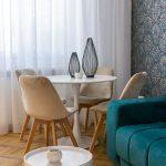 Obývačka s veľkoformátovou modrou vzorovanou tapetou, rozkladacou modrou sedačkou a jedálenským kútom s čalúnenými stoličkami.