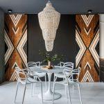 """interiér kuchyne s ikonickým stolom Tulip a stoličkami Masters, s čiernym stropom, stenou a kuchynskou linkou, mohutným elegantným lustrom zloženým zo sklených korálok a posuvnými masívnymi dverami """"barn doors"""" s geometrickým vzorom"""