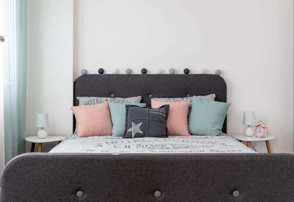 Spálňa zariadená vo vintage štýle v odtieňoch sivej, bielej, ružovej a mentolovej s čalúnenou posteľou.