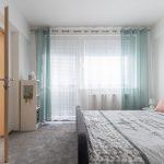 Vintage spálňa so sivým kobercom, čalúnenou posteľou a mentolovými závesmi.