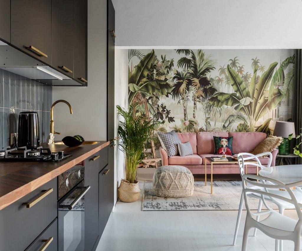Priestor kuchyne prepojenej s obývačkou. V kuchyni je čierna kuchynská linka, v obývačke je tapeta s motívom tropickým rastlín, staroružová pohovka a textílie z prírodných materiálov.