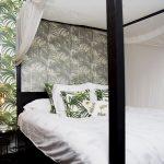 spálňa s motívom paliem na tapete aj posteľnom prádle a s masívnou tmavou posteľou s nebesami