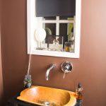 kúpeľňa v koloniálnom štýle s hnedou stenou, zabudovaným vodovodným kohútikom a dávkovačom mydla v stene, s tmavou skrinkou a dreveným lakovaným umývadlom vsadeným do skrinky