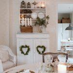 vianočný interiér v škandinávskom vidieckom štýle, so sviatočne prestretým stolom v prírodnom duchu, s bielou skriňou, na ktorej sú zavesené prírodné vence v tvare srdca, s bielou policou s taniermi, svietnikmi a petrolejovými lampami, na skrini je váza s čečinou a adventný svietnik