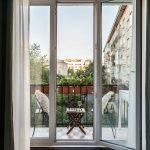 presklené dvere vedúce na balkón s dreveným stolíkom a dvoma stoličkami