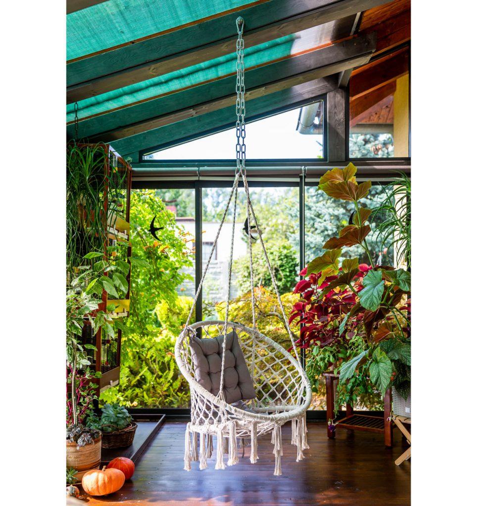 zimná presklená záhrada s tropickými rastlinami, sukulentmi, klietkami s vtákmi a závesnou hojdačkou