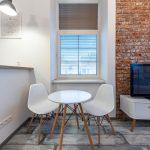 interiér malého bytu v industriálnom štýle s hrubými múrmi a tehlovou stenou