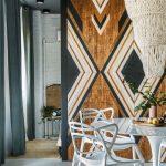 interiér s bielym jedálenským stolom a stoličkami, masívnymi posuvnými dverami oddeľujúcimi spálňu od kuchyne a korálkovým mohutným bielym lustrom