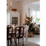 škandinávsky vidiecky interiér s bielym stolom, drevenými stoličkami, bielym kredencom, so sviatočným vianočným prestieraním a živým vianočným stromčekom v kvetináči