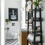 kúpeľňa s čiernym regálom, skrinkou s umývadlom, závesným WC a dlažbou s 3D ilúziou