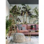 obývačka s veľkoplošnou tapetou s florálnymi motívmi, staroružovou pohovkou, taburetkou z prírodného materiálu, mosadzným stolíkom a dekoratívnym dreveným stojanom na plátno