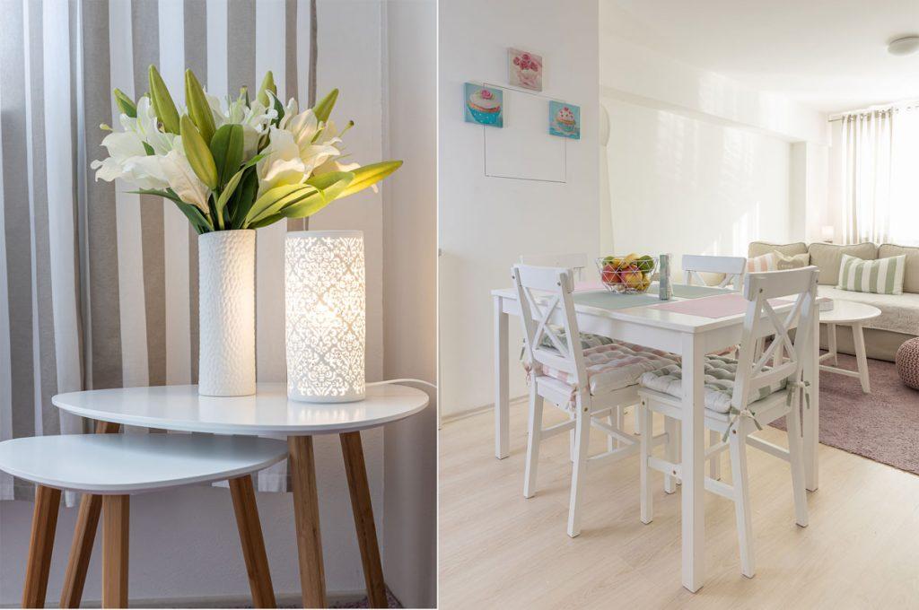 jedáleň v malom byte vo vidieckom štýle prepojená s obývačkou, s bielym dreveným stolom a stoličkami a pastelovým prestieraním. Biele stolíky s bielou vázou s kvetmi a bielym svietidlom.