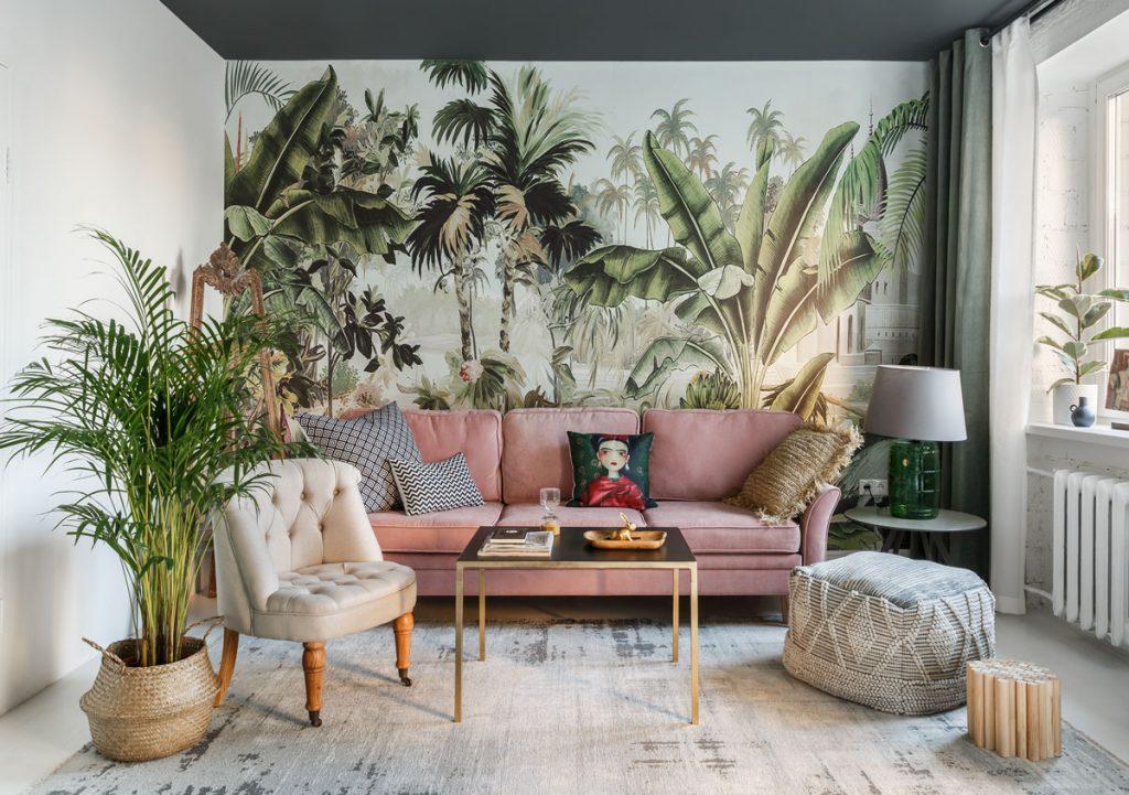 obývačka s veľkoplošnou tapetou s tropickými rastlinnými motívmi, staroružovou pohovkou, koženým maslovým kreslom, drevenou taburetkou, taburetkou z prírodného materiálu, mosadzným stolíkom, lampou zo zeleného skla a dekoratívnym dreveným stojanom na plátno