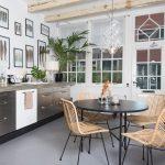 kuchyňa s kuchynskou linkou v kovovom vzhľade a kamennou pracovnou doskou, s prútenými kreslami, čiernym jedálenským stolom, obrazmi s vtáčími perami a drevenými stropnými trámami