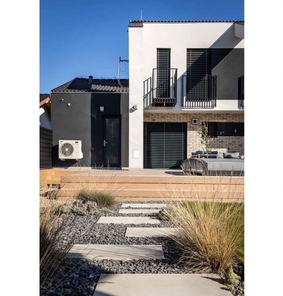 Rodinný dom s vyvýšenou terasou, štrkovou cestičkou a okrasnými trávami.
