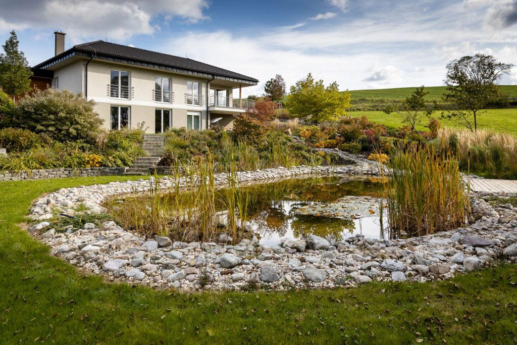 rodinný dom s prírodnou záhradou vo svahu vsadenou do okolitej prírody, s jazierkom, múrikmi s andezitu, kamennými chodníčkami a trvalkovými záhonmi