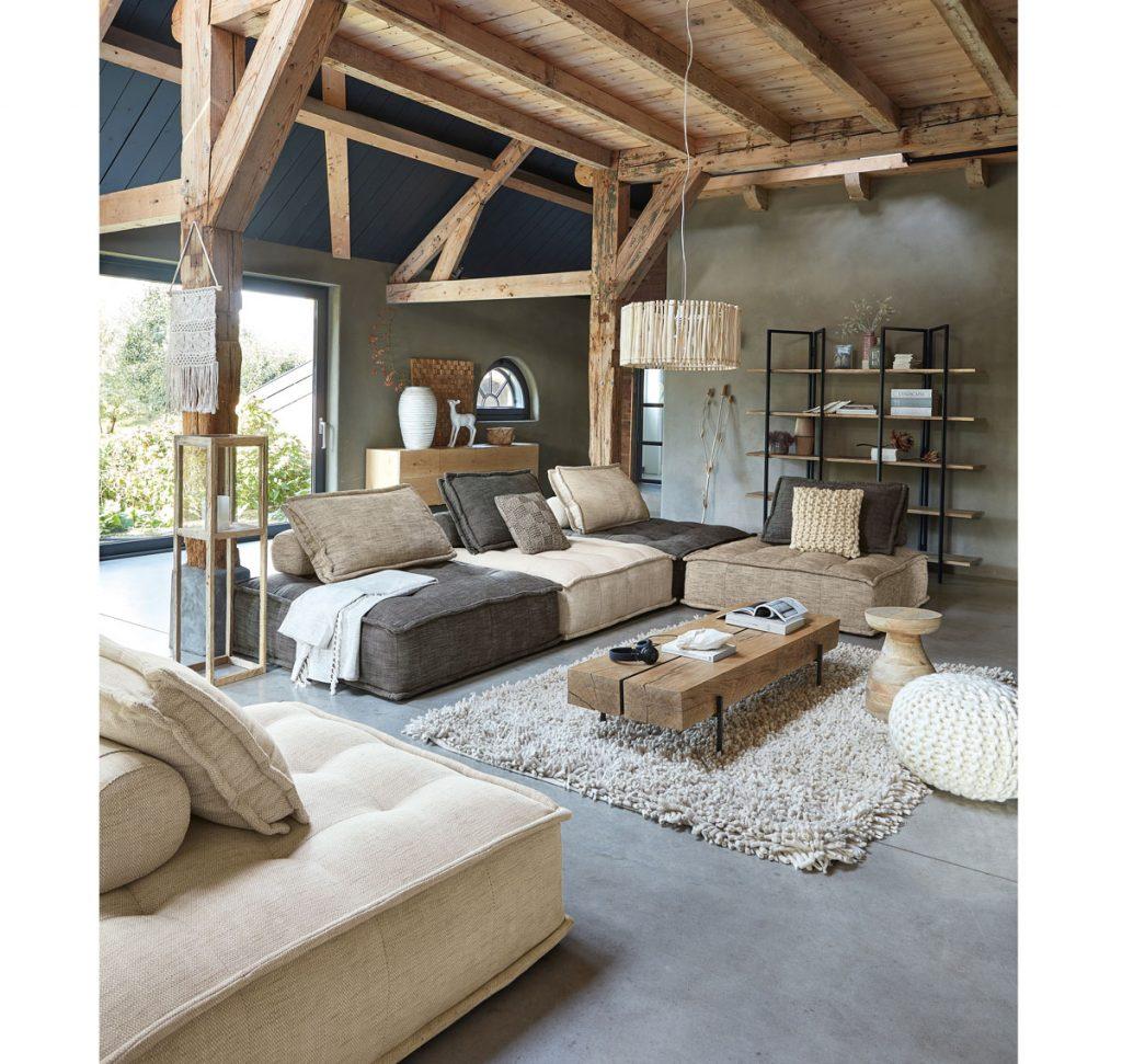 Trendy v interiéri 2020: Obývačka v prírodnom štýle s veľkou pohovkou v zemitých farbách, dreveným stolíkom, kovovým regálom a dreveným lustrom.