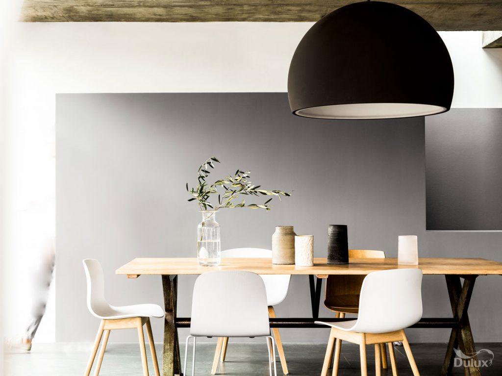 jedáleň v severskom štýle s čiernym svietidlom, bielymi stoličkami a svetlým dreveným stolom