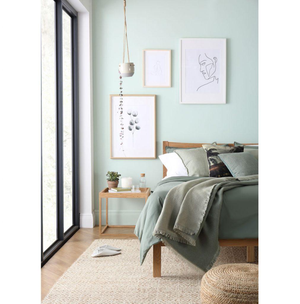 spálňa zariadená v odtieni mätovo sivej, s pastelovo zelenou stenou, drevenou posteľou a stolíkom, a textíliami v mätovo zelených odtieňoch