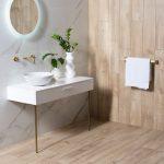 Interiérové trendy 2020: kúpeľňa s bielym umývadlom a stolíkom na nožičkách a s dreveným obložením.