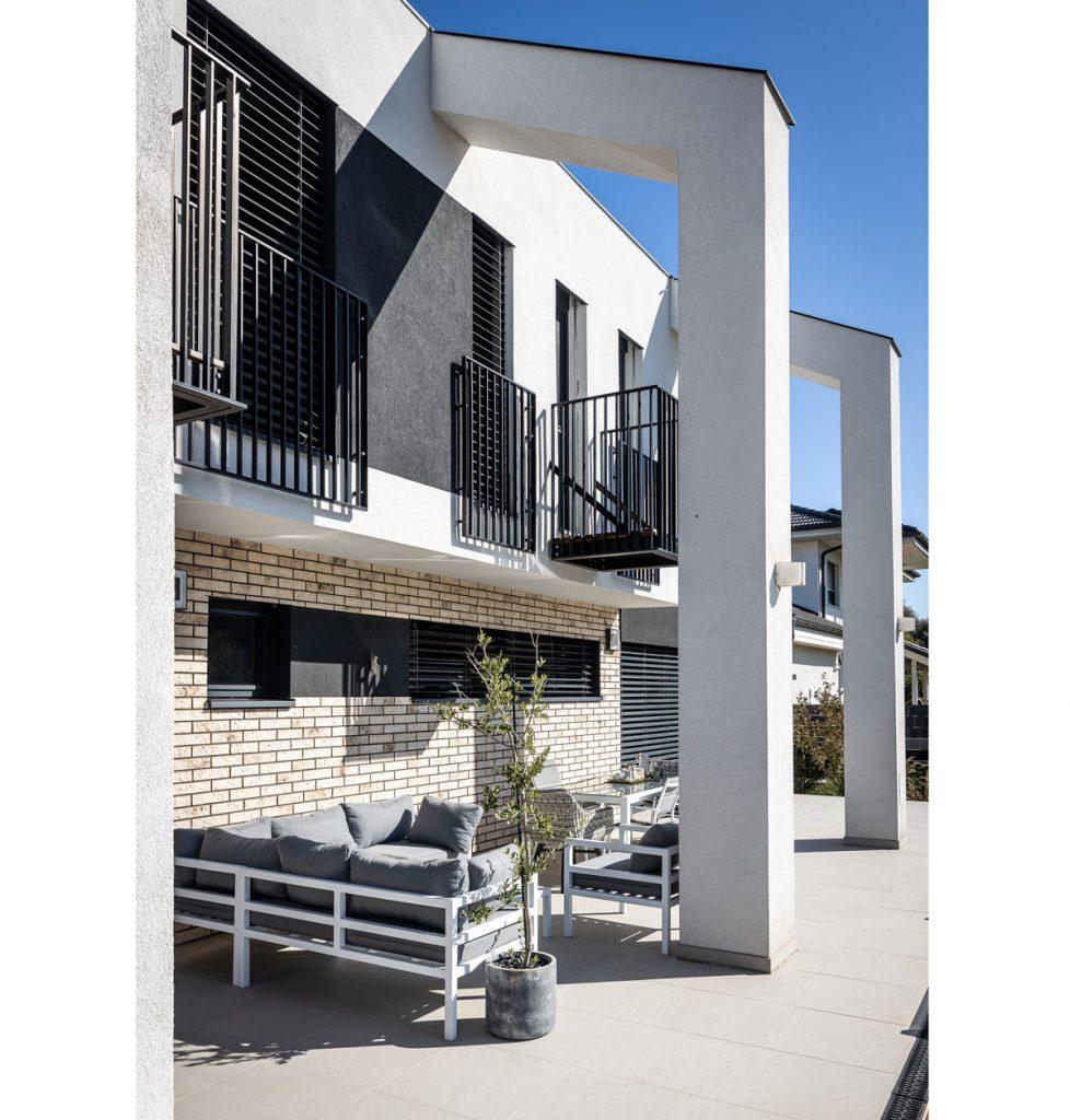 Moderný rodinný dom s členitou fasádou a slnečnou terasou s posedením.