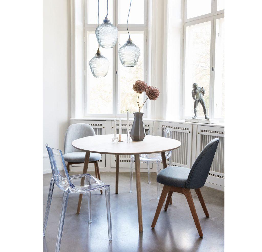 interiér s priehľadnými svietidlami, čalúnenými stoličkami, priehľadnou modrou plastovou stoličkou a okrúhlym stolom