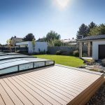 Malá moderná záhrada pri rodinnom dome s trávnatou plochou, záhradným domčekom, stupňovitou terasou a zastrešeným bazénom.