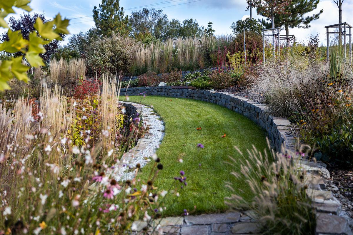 Prírodná záhrada s trvalkovými záhonmi ohraničenými kamennými múrikmi s priznanou štrkovou drenážou.